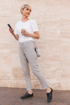 Stylish blond woman wearing white t-shirt using cell phone, while standing against beige wall outdoor in summer and looking aside at copyspace with takeaway coffee