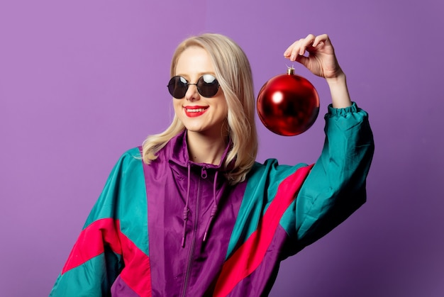 Stylish blonde in 80s windbreaker and roud sunglasses holds christmas bauble on purple wall
