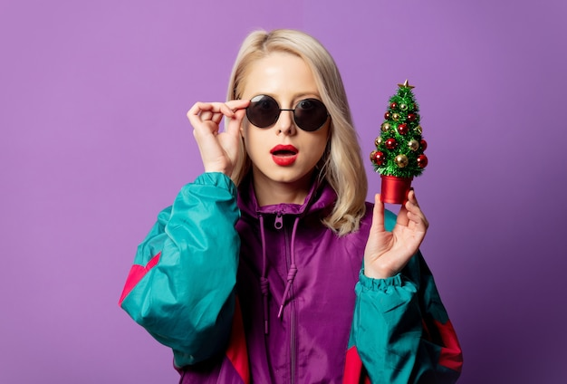 Stylish blonde in 80s windbreaker and roud sunglasses holds christmas tree on purple wall