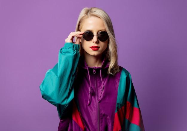Stylish blonde in 80s windbreaker and round sunglasses on purple wall