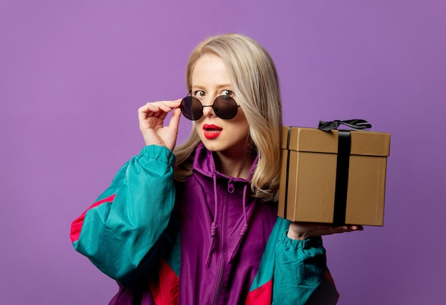 Stylish blonde in 80s windbreaker and round sunglasses with gift box on purple wall