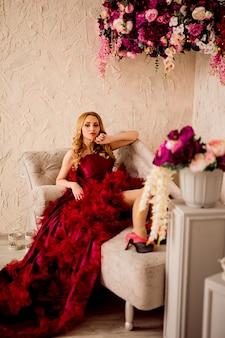 Stylish blonde beautiful woman on the sofa in burgundy dress
