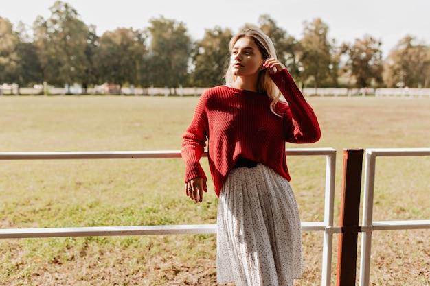 秋の田園地帯で明るい太陽を楽しむスタイリッシュなブロンド。赤いプルオーバーと白いドレスの屋外で喜んでポーズをとる美しい少女。
