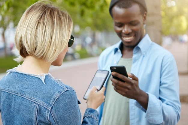 Stylish blonde female in denim jacket and sunglasses meeting her african male friend on street, holding cell phones in hands, exchanging their telephone numbers in oder to keep their relations