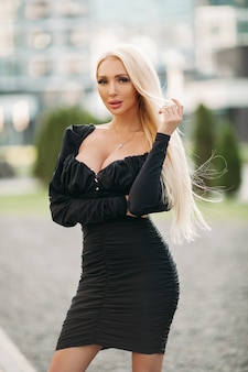 Stylish blonde female model in black dress posing at camera while standing outdoors. style and fashion concept