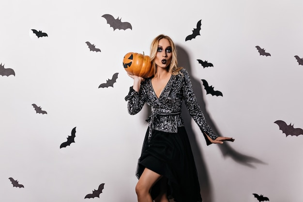 Stylish blonde girl in black dress posing at witch party. elegant female model with dark makeup holding big halloween pumpkin.