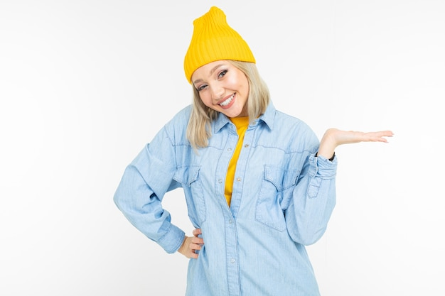 Stylish blonde girl in casual look with holding hand with a template on a white background