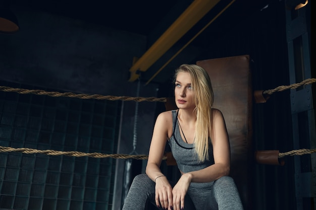 Stylish blonde girl in her twenties sitting on leather chair in the corner of boxing ring
