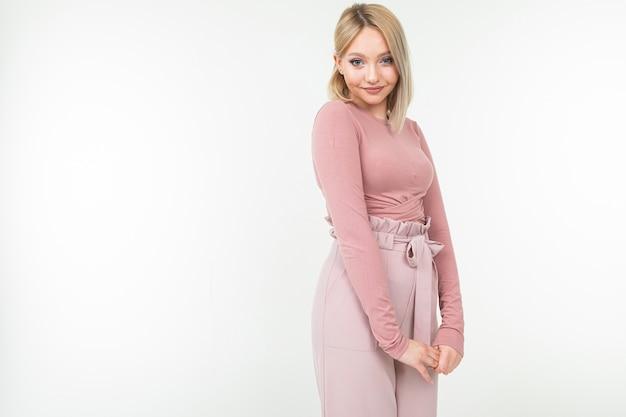 Стильная блондинка в розовой блузке позирует