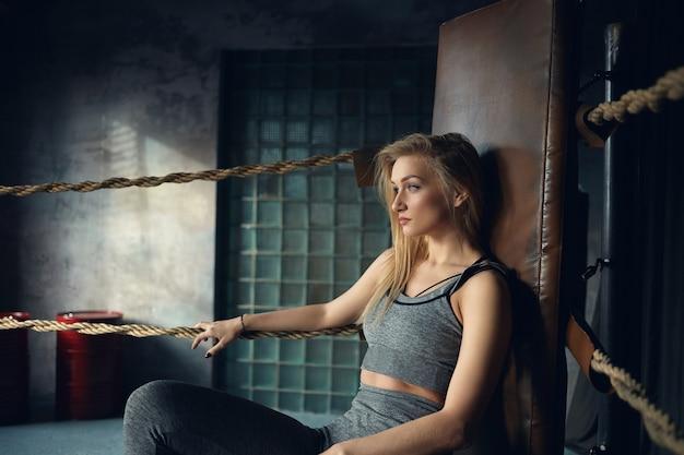 복싱 링의 모서리에있는 가죽 의자에 앉아 그녀의 20 대 세련된 금발 소녀