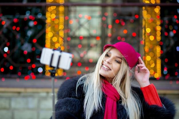 花輪で飾られた街の通りで自分撮りをして、面白い帽子をかぶってスタイリッシュなブロンドの女の子の観光客。テキスト用のスペース