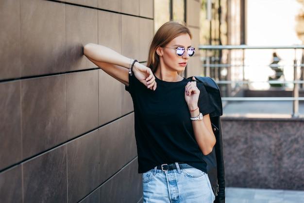 Стильная блондинка в черной футболке и очках позирует на улице