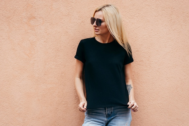 Stylish blonde girl wearing black t-shirt and glasses posing against wall