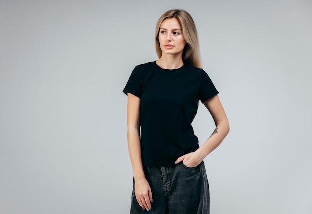 黒のtシャツのポーズを着てスタイリッシュなブロンドの女の子