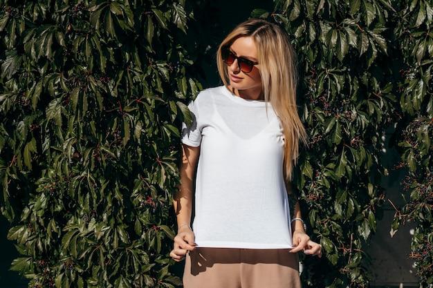 Стильная блондинка в белой футболке и очках