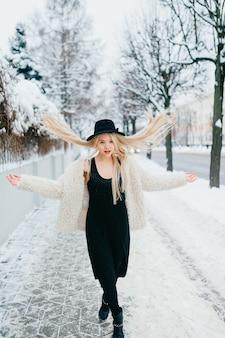 긴 비행 머리 거리에서 포즈를 취하는 세련된 금발 소녀