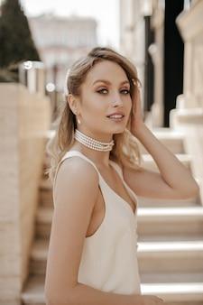 真珠のネックレスと白いドレスの美しい化粧をしたスタイリッシュな金髪の灰色の目の女性がカメラをのぞき、外で微笑む