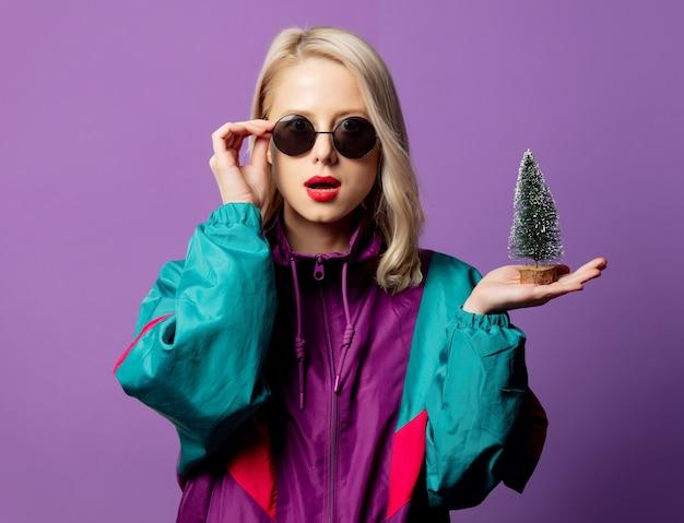 Стильная блондинка в ветровке 80-х и круглых солнцезащитных очках с елкой на фиолетовой стене