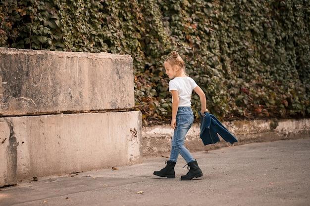 Стильная блондинка маленькая девочка в джинсах и белой футболке идет по улице. девочка 7 лет маленькая модель, красивый ребенок