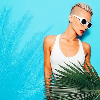 白い水着のスタイリッシュな金髪モデル。ビーチの熱帯の雰囲気