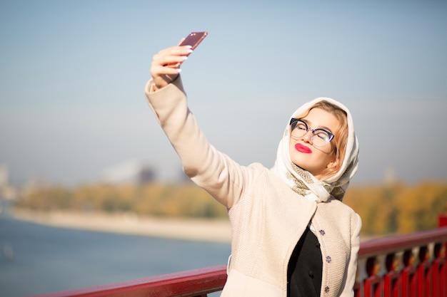 スマートフォンで自分撮りをしているスタイリッシュな金髪モデルの観光客。女性はショールと眼鏡をかけています