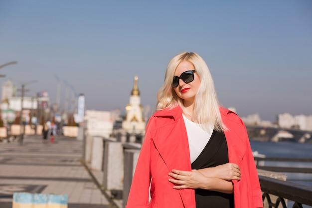 세련된 금발 모델은 선글라스를 착용하고 흐릿한 다리 배경에 빨간 망토를 입고 포즈를 취합니다