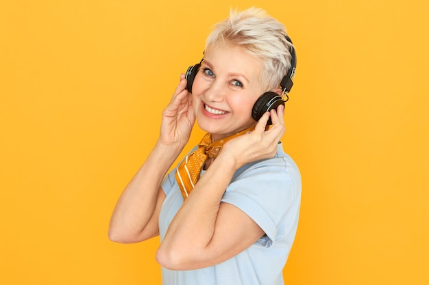 Stylish blonde retired woman enjoying music, listening to radio in wirless headphones posing agaisnt yellow