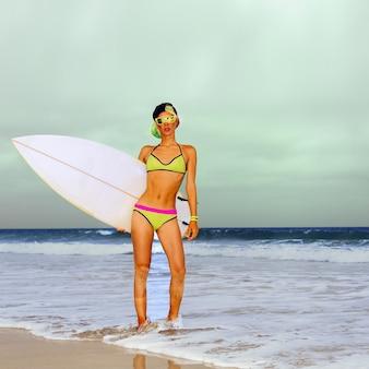 サーフボードとビーチに立っているスタイリッシュなブロンド。