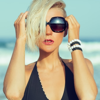 Stylish blonde walking on the beach in fashion accessories