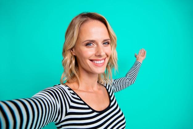 Стильная блондинка в полосатом свитере позирует у синей стены