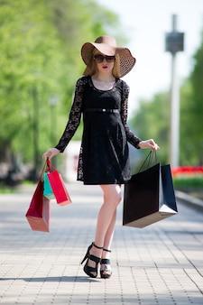 검은 드레스, 선글라스와 도시에서 산책하는 쇼핑백과 모자에 세련된 금발의 여자, 휴일 콘서트