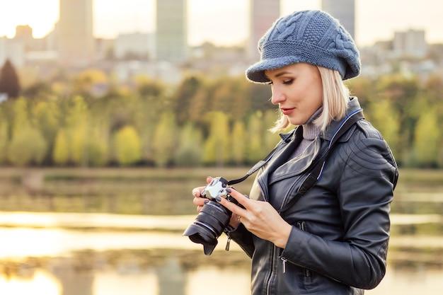 Стильная блондинка в синем французском берете фотограф фотографирует осенний лес на закате