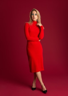 赤い壁に分離されたポーズの赤い秋の冬のファッションドレスのスタイリッシュなブロンドの女性