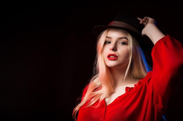 彼女の顔に影を付けてスタジオでポーズをとって赤いブラウスと茶色の帽子のスタイリッシュなブロンドの女性