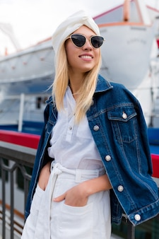白いショートパンツと黒いメガネのシャツを着て日没時に夏の街の通りで屋外のヨットクラブでポーズをとるスタイリッシュなブロンドの女性。休暇の気分、旅行