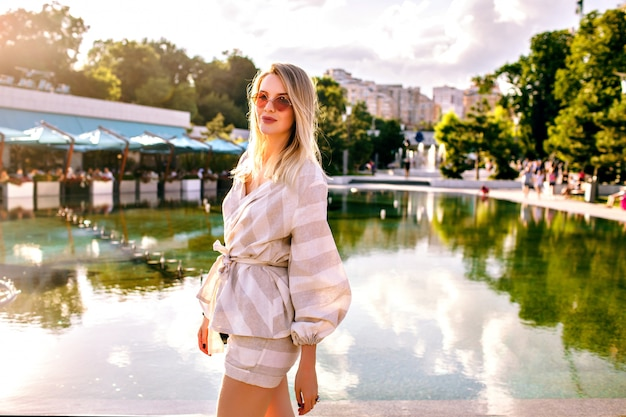 Стильная блондинка позирует на улице в солнечный весенний день, в модном бежевом костюме и аксессуарах
