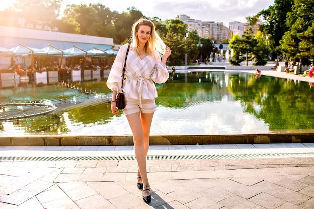 スタイリッシュな金髪女性が晴れた春の日に路上でポーズ、トレンディなベージュのスーツとアクセサリーを着て