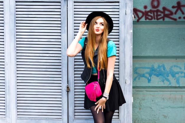Стильная блондинка позирует на улице, одетая в яркий хипстерский наряд, игривые крутые эмоции, веселье, удовольствие, счастливые каникулы в одиночестве, винтажная шляпа и мини-юбка.