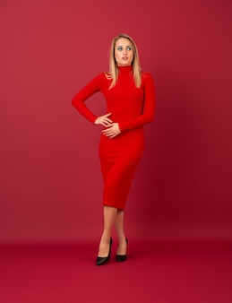 Stylish blonde woman in red autumn winter fashion dress posing isolated  on red wall