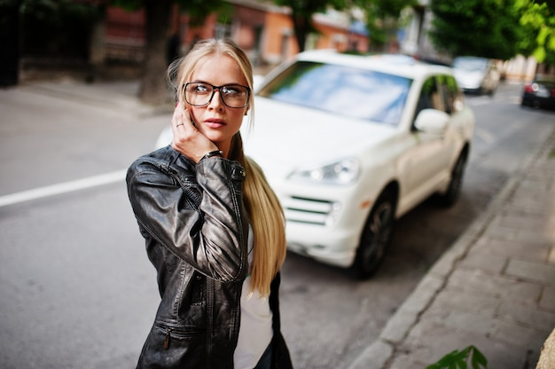 Stylish blonde woman wear at jeans, glasses and leather jacket with mobile phone, against luxury car