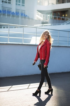 Stylish blonde woman wearing red jacket walking down the street with sun light