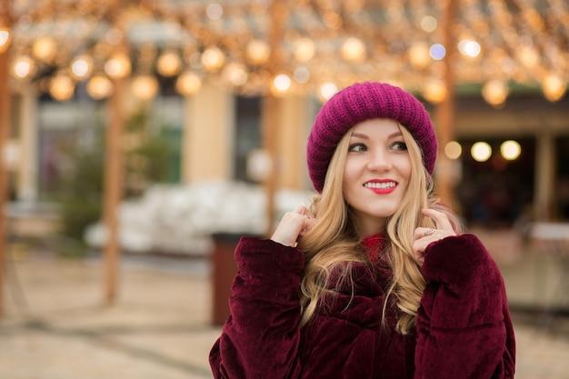 キエフの通りで花輪の背景にポーズをとって、赤いニット帽と冬のコートを着てスタイリッシュな金髪の女性