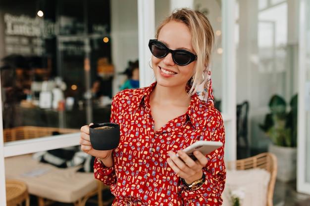 Elegante donna bionda che indossa abiti estivi luminosi utilizzando smartphone e bere caffè all'esterno