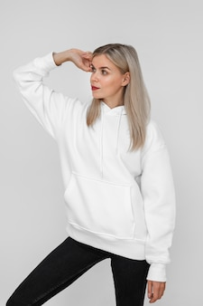 Elegante donna bionda che indossa una felpa con cappuccio bianca