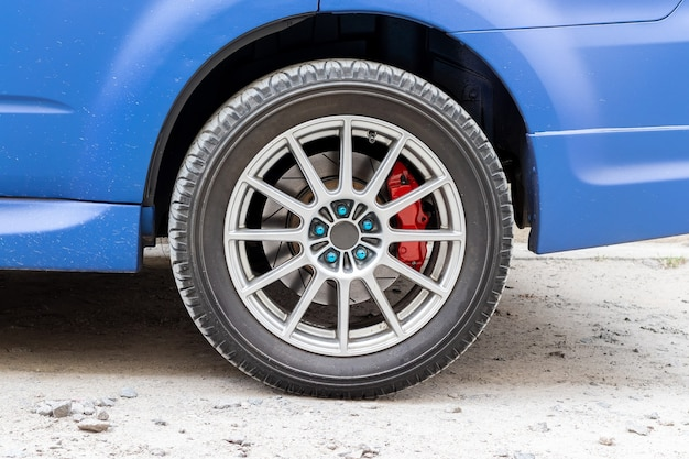 Stylish blue car wheel with red brake caliper and five-nut rim