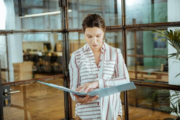 Стильные синие серьги. красивая зрелая женщина, носящая красивые стильные синие серьги, работает в офисе