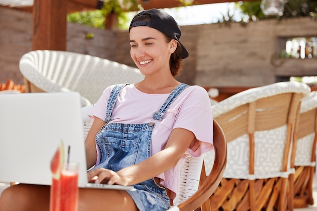 Стильная голубоглазая красивая женщина-фрилансер проверяет электронную почту на портативном компьютере, использует приложение на современном устройстве