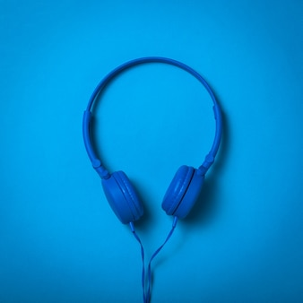 Stylish blue headphones with a wire on a blue surface. mobile audio playback equipment.
