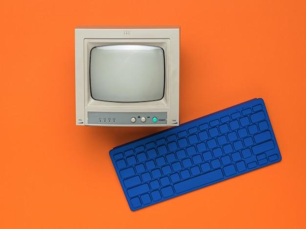Стильная синяя клавиатура и небольшой монитор на оранжевом фоне.