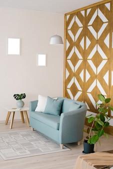 枕、コーヒーテーブル、リビングルームの花瓶のイチジク、カーペットが付いているスタイリッシュな青いソファ。ベージュの壁のある部屋の木製装飾壁